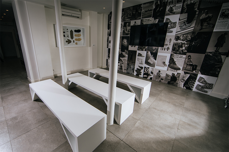 Showroom for Clarks, with three white benches, television and wall vinyl, black and white photography