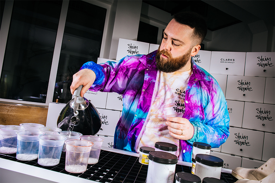 Tie dye artist Stain Shade holding a kettle and using hot water to mix dye, creating bespoke fashion items for Clarks Originals